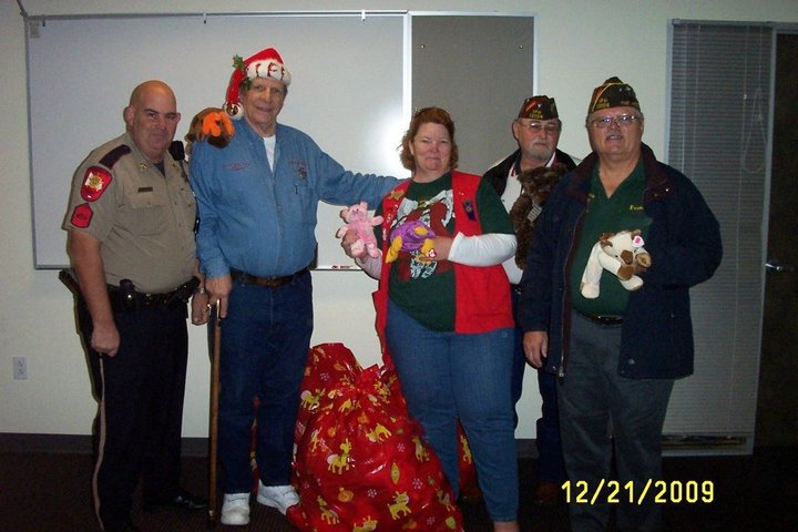 Click to View Photo Gallery - Lee Derby, Judy Brawner, Norm Brawner, and Everett Ison donating to the Sheriff's Department Hug A Bears